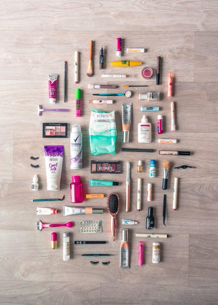 Zdjęcie z góry - pokazujące dużą ilość kosmetyków pielęgnacyjnych i do makijażu, ułożonych na podłodze.