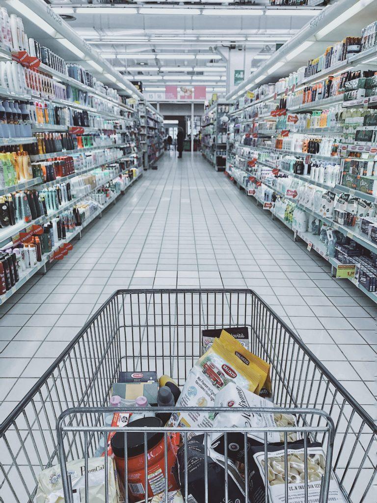 Wózek sklepowy z produktami w środku, przemierzający alejki supermarketu.