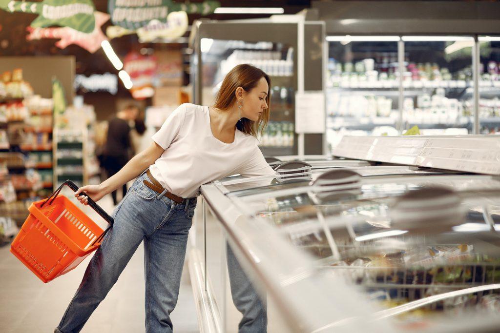 Kobieta na zakupach - z plastikowym koszykiem w jednej ręce, drugą sięga do zamrażarki.