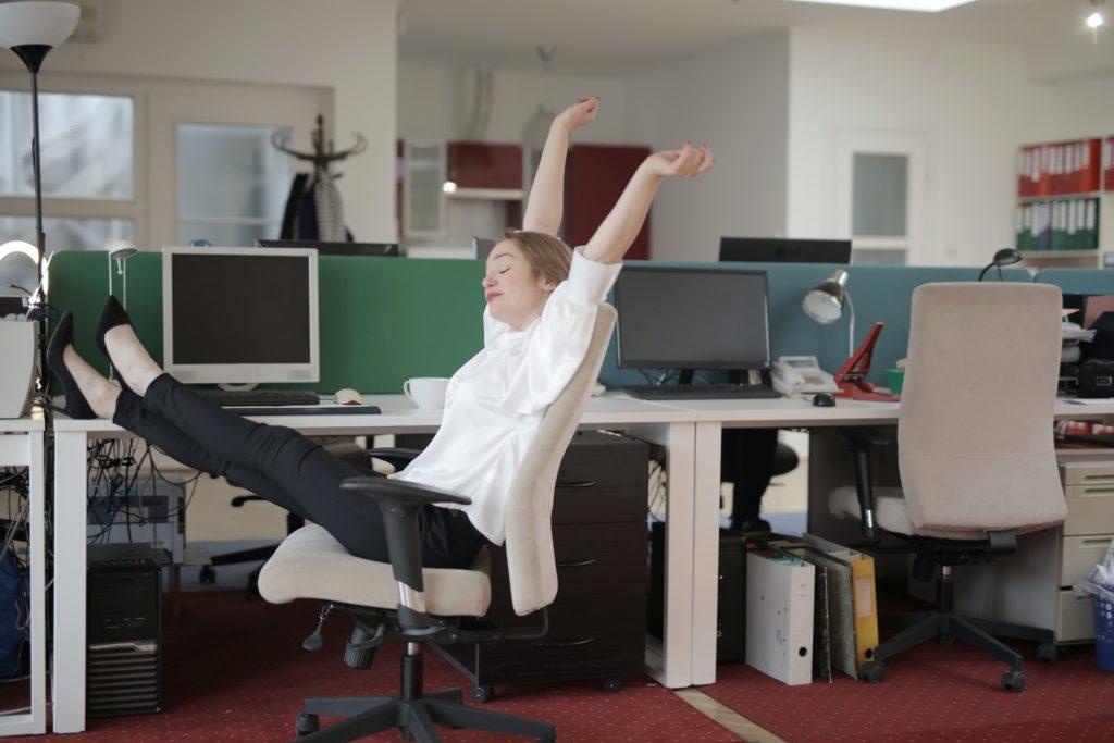 Kobieta przeciągająca się siedząc na krześle przy biurku.