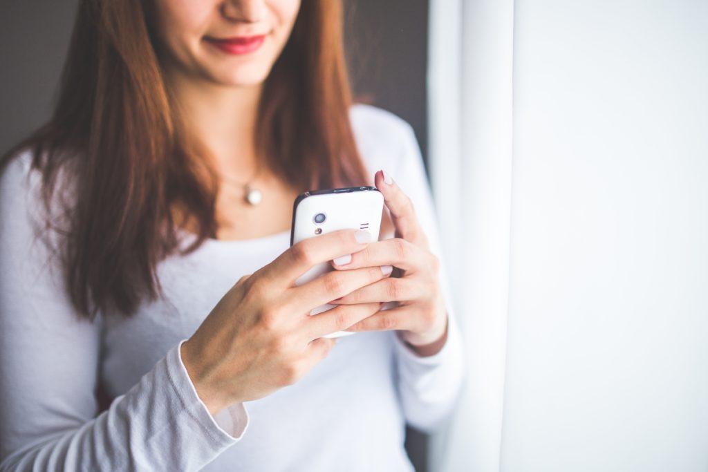 Kobieta trzymająca biały telefon.