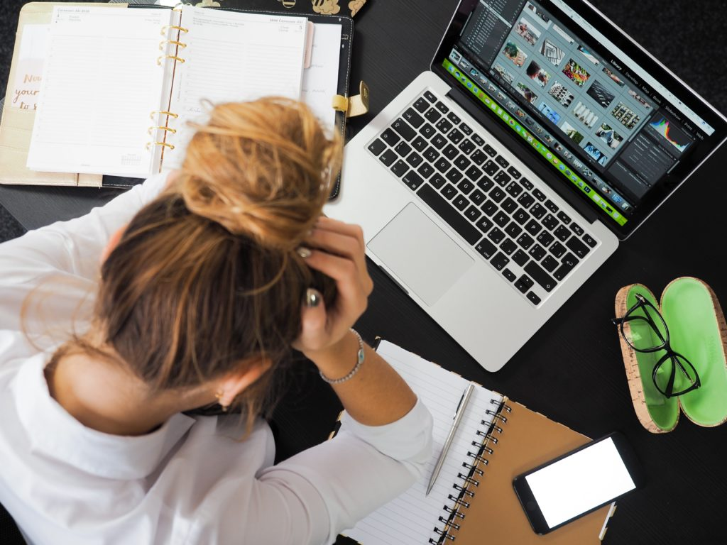 Kobieta oparta o biurko, trzymająca się za głowę. Na biurku, komputer, notes, telefon notatnik i okulary.