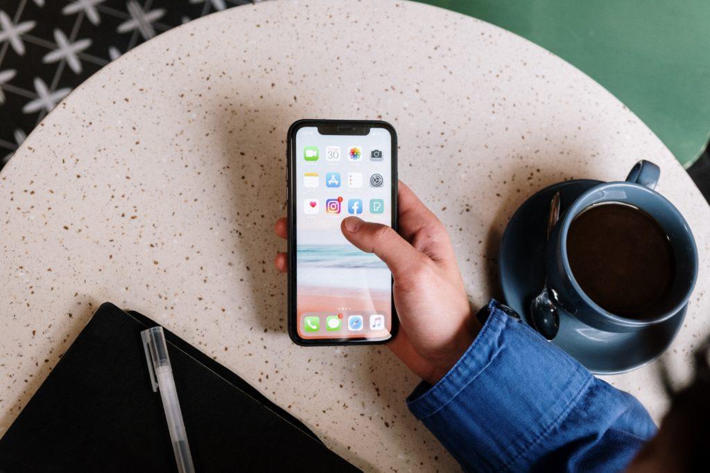 Dłoń trzymająca telefon z widocznymi ikonkami aplikacji social media.