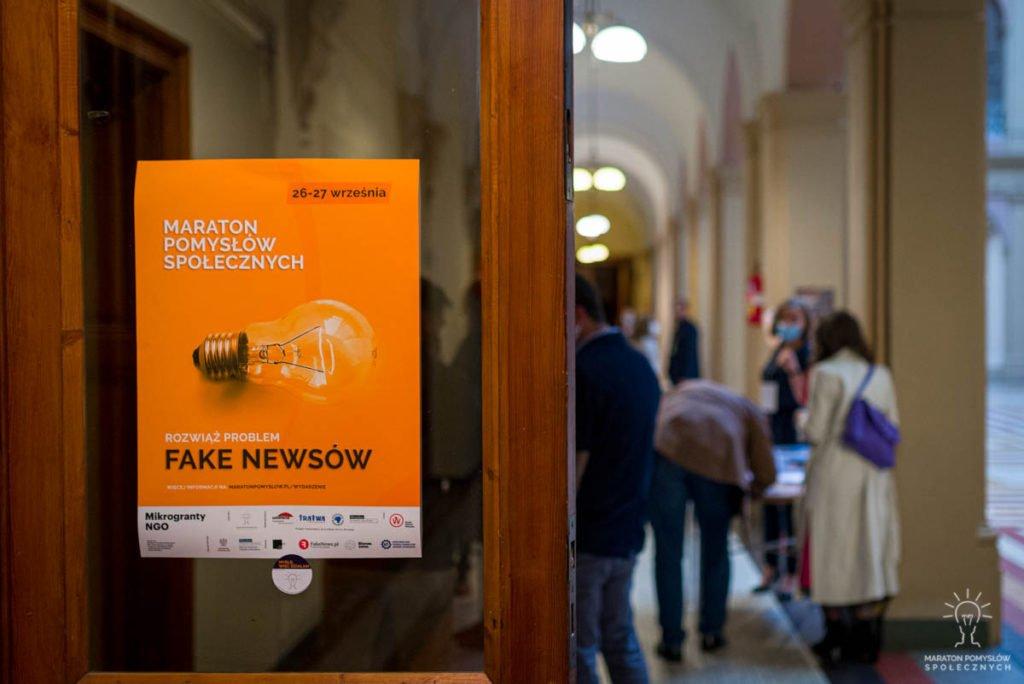Plakat wydarzenia - Maraton Pomysłów Społecznych: Fake newsy na drzwiach. W tle goście wydarzenia w trakcie gali finałowej w NOT Wrocław.