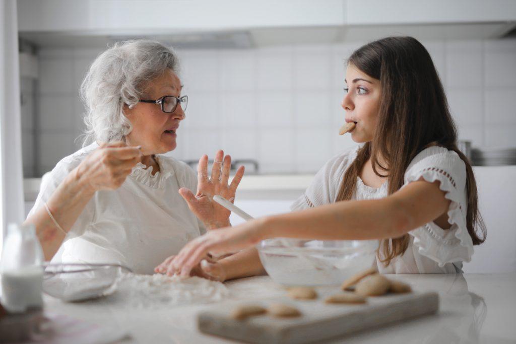 Babcia i wnuczka siedzące przy stole w trakcie gotowania. Wnuczka trzyma w ustach ciastko. Babcia tłumaczy jej coś.