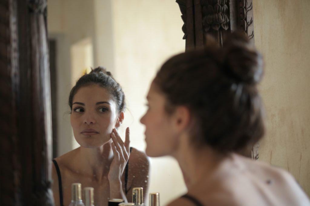 Młoda kobieta przeglądająca się w lustrze.