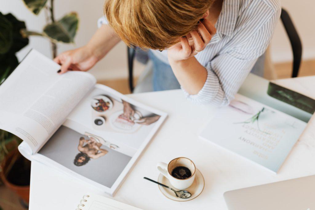 Kobieta siedząca przy stole przeglądająca czasopismo przy filiżance kawy (widok z góry).